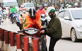 Chùm ảnh: Người dân Hà Nội khoác cả chăn bông, mặc áo mưa xuống phố để tránh rét