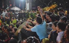 Người dân ném tiền vào kiệu ấn trước giờ khai hội tại Đền Trần