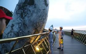 Tròn một ngày sau khi bị vẽ bậy, Cầu Vàng Đà Nẵng đã được các công nhân sơn sửa lại