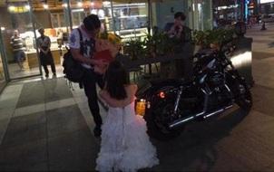 Cô gái mặc váy cưới trắng, cưỡi motor, cầm sổ hộ khẩu cầu hôn bạn trai ngay giữa quảng trường