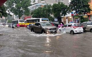 Clip: Đường Hà Nội biến thành sông sau cơn mưa, xe máy và ô tô chật vật vượt qua đoạn đường ngập