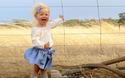 Bức ảnh bé gái vui chơi bên đồng cỏ thật yên bình nhưng có cái gì đó không ổn