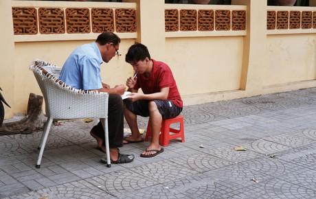 """""""Lớp học"""" đáng yêu trên vỉa hè: Một bác bảo vệ vừa giữ xe vừa dạy chữ cho cậu nhóc bán hàng rong ở Sài Gòn"""