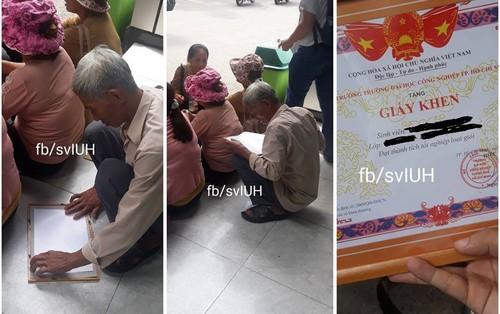 Bức ảnh người cha già ngồi bệt giữa sân trường nâng niu giấy khen tốt nghiệp loại giỏi của con gái khiến dân mạng xót xa