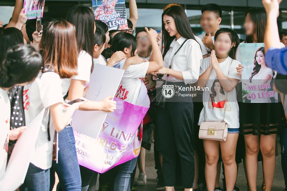 Hoa hậu Mỹ Linh diện trang phục đơn giản, tươi tắn bên mẹ và người hâm mộ tại sân bay Tân Sơn Nhất - Ảnh 2.