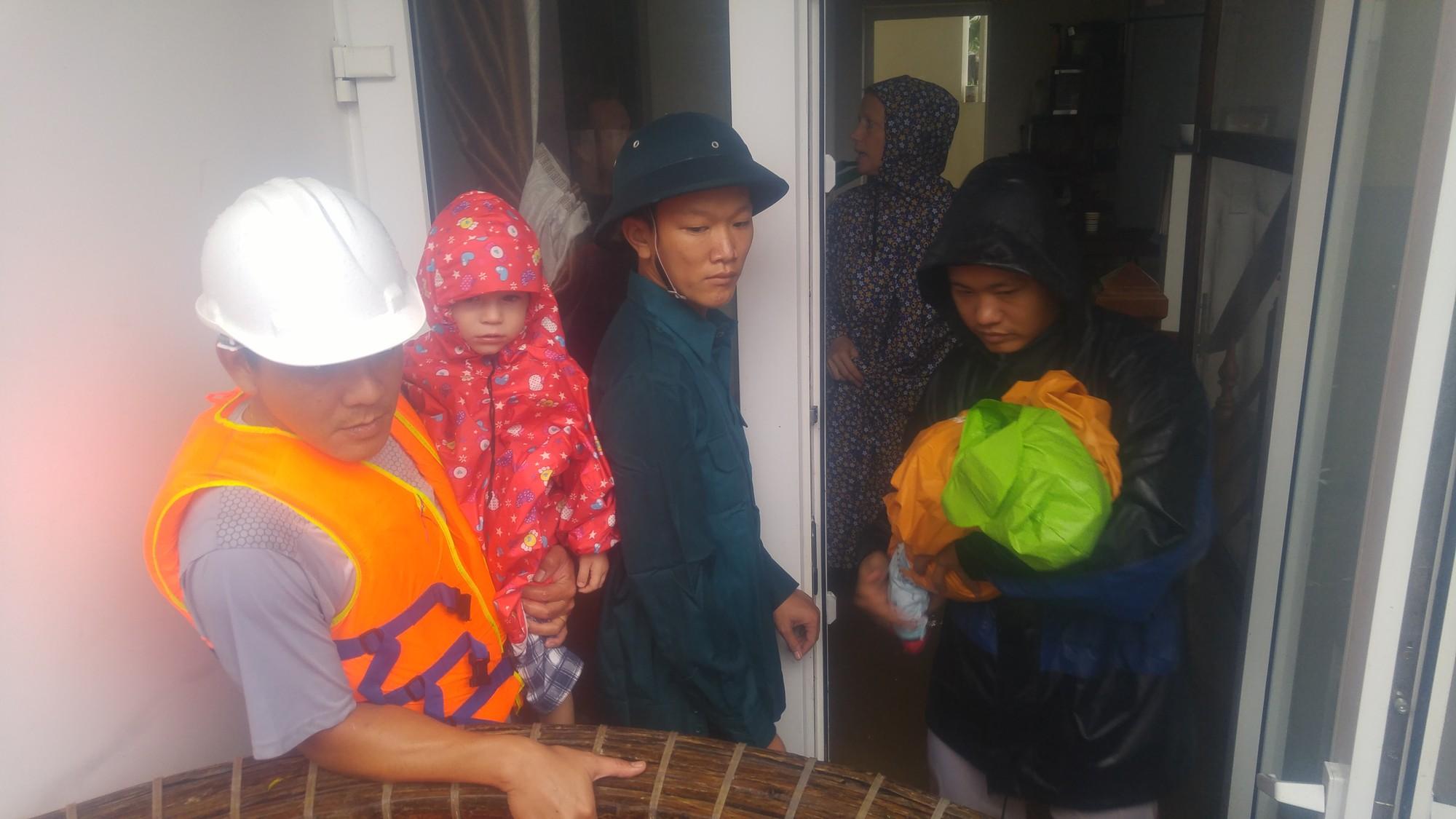 Dùng thuyền thúng cứu 2 mẹ con người nước ngoài ra khỏi căn nhà ngập lụt ở Hội An - Ảnh 1.