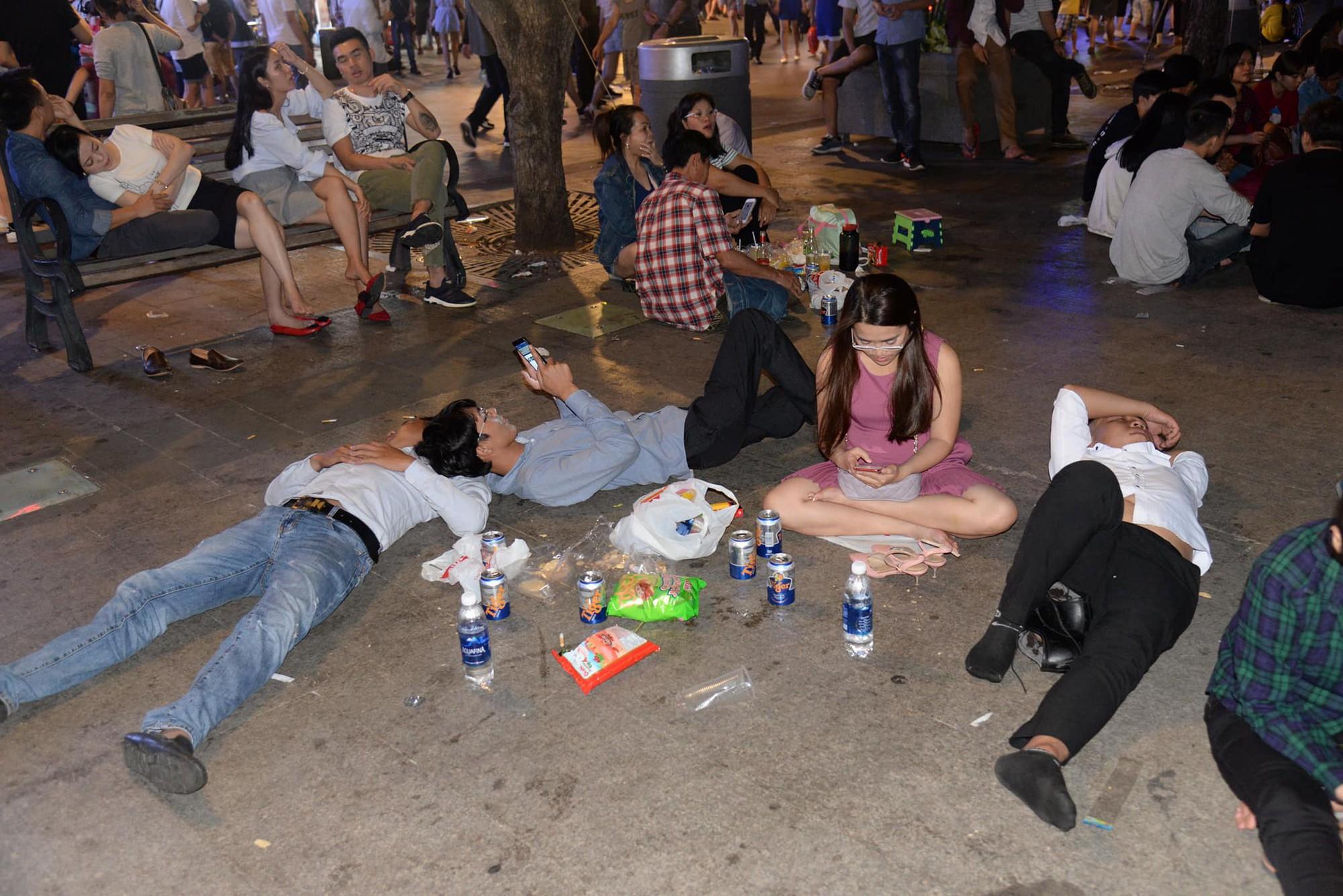 Hình ảnh nhìn thôi đã mệt: Thanh niên say bét nhè nằm lăn ra giữa phố đi bộ, trẻ con đi theo bố mẹ vạ vật chờ giao thừa - Ảnh 7.