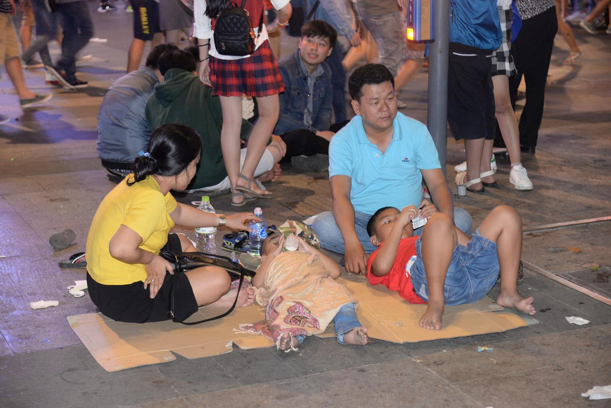 Hình ảnh nhìn thôi đã mệt: Thanh niên say bét nhè nằm lăn ra giữa phố đi bộ, trẻ con đi theo bố mẹ vạ vật chờ giao thừa - Ảnh 6.