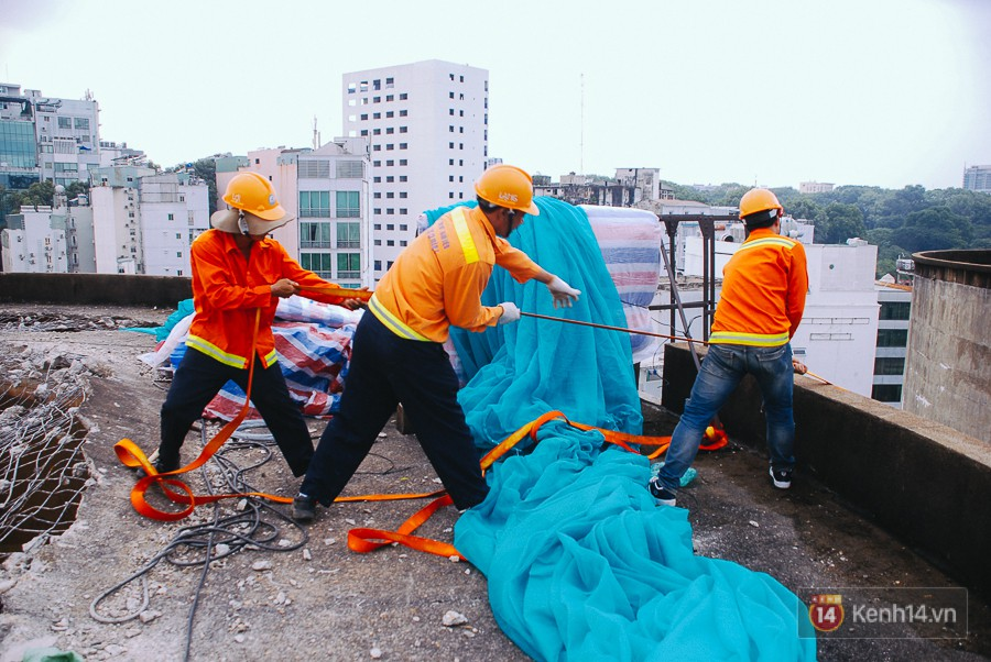 Các công nhân vận chuyển giàn giáo bằng dây kéo từ dưới đất lên.