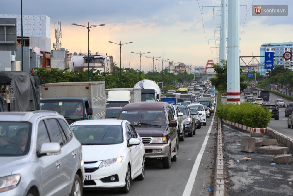 Kẹt xe kéo dài hơn 2km trên đại lộ Phạm Văn Đồng sau cơn mưa lớn ở Sài Gòn - Ảnh 2.