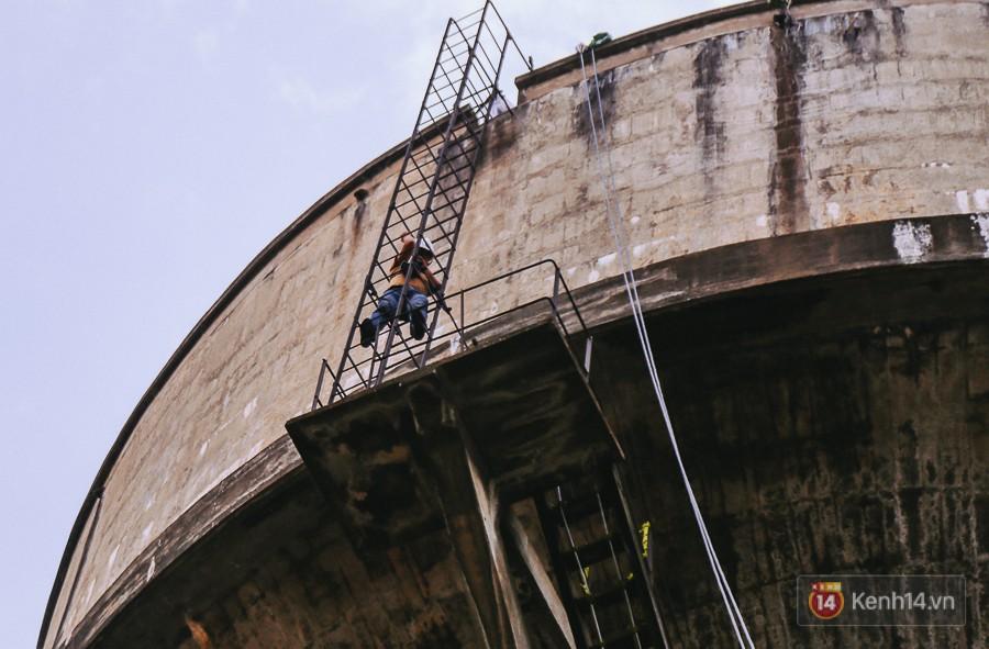 Việc di chuyển lên thuỷ đài để tháo dỡ phần mái phải tận dụng lối đi thang sắt chật hẹp.
