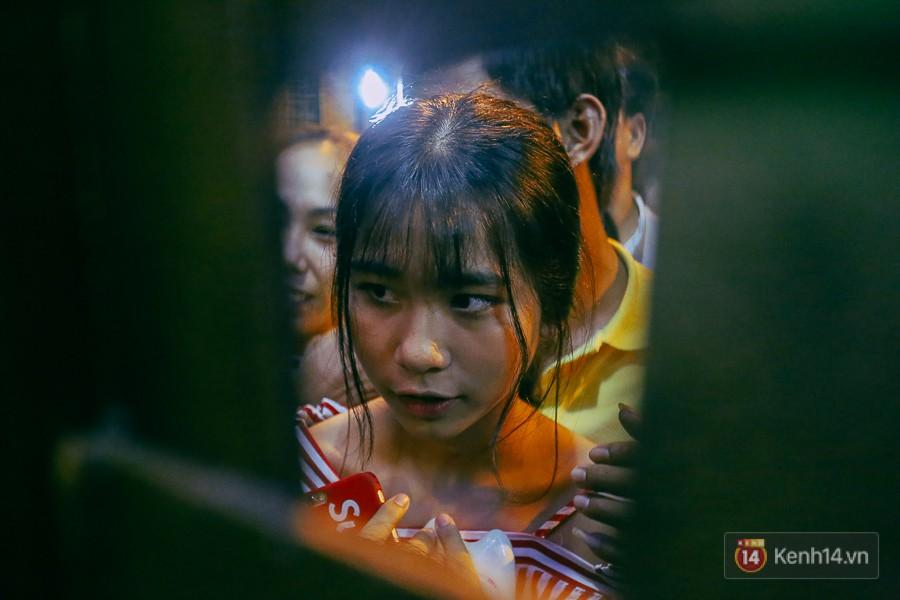 Cô gái hồi hộp chờ trước cửa để chuẩn bị ùa vào khi bảo vệ mở cổng.