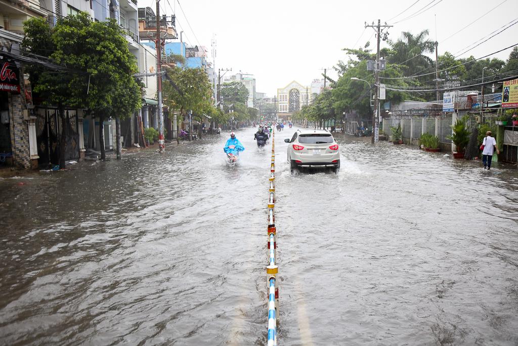 Học sinh ở Sài Gòn bì bõm lội nước sau giờ tan học do mưa lớn kéo dài từ sáng đến trưa - Ảnh 6.
