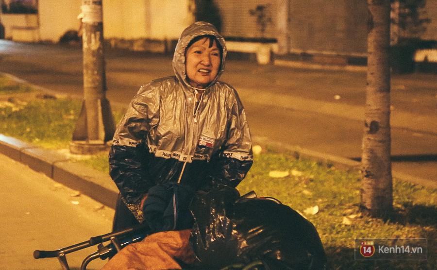Bà Loan mưu sinh bằng nghề ve chai cũng mặc áo mưa để chống lạnh.