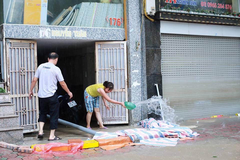 Chùm ảnh: Người Hà Nội mặc áo mưa ăn trưa giữa đường phố ngập lênh láng - Ảnh 13.
