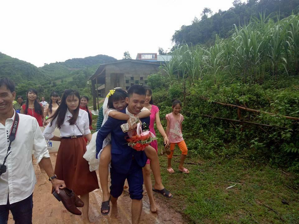 Đám cưới mùa mưa bão: Chú rể hạnh phúc cõng cô dâu qua đoạn đường ngập nước và bùn đất - Ảnh 2.