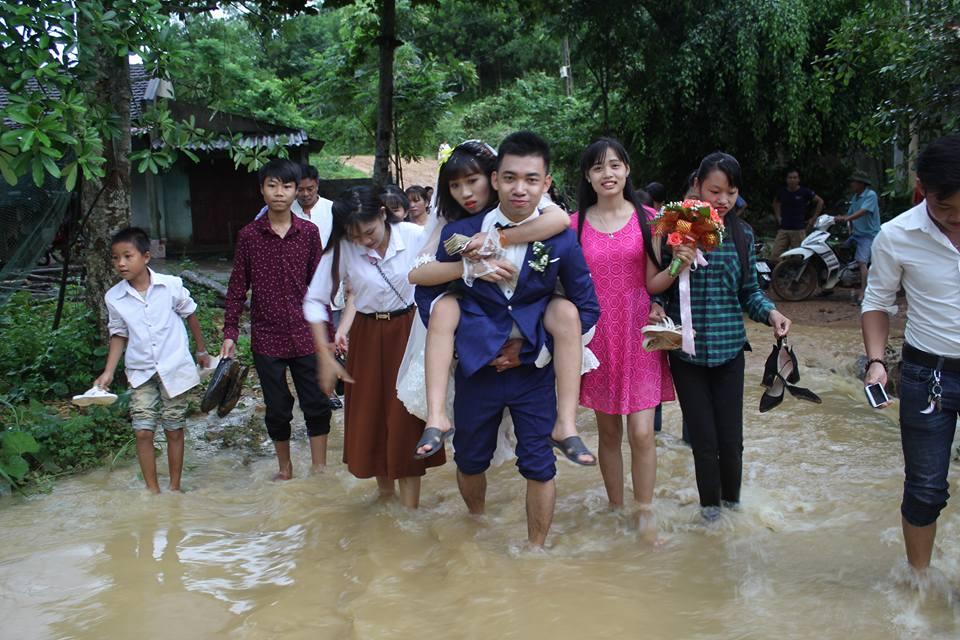 Đám cưới mùa mưa bão: Chú rể hạnh phúc cõng cô dâu qua đoạn đường ngập nước và bùn đất - Ảnh 4.