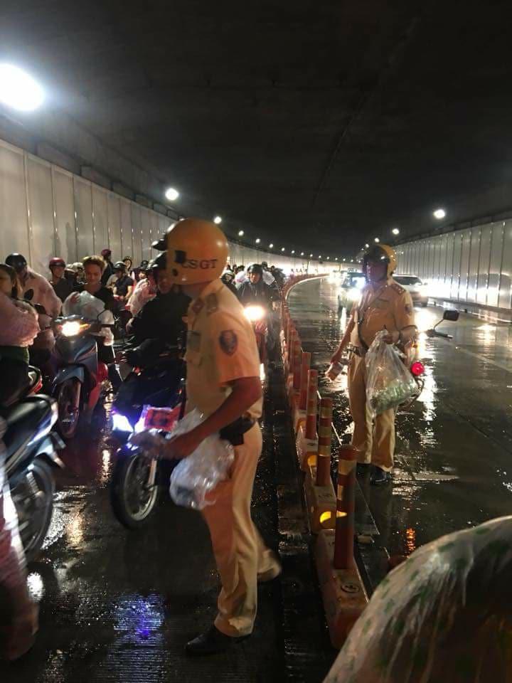 Hình ảnh đẹp đêm trung thu ở Sài Gòn: 2 chiến sĩ CSGT phát áo mưa miễn phí cho người dân trong hầm Thủ Thiêm - Ảnh 1.