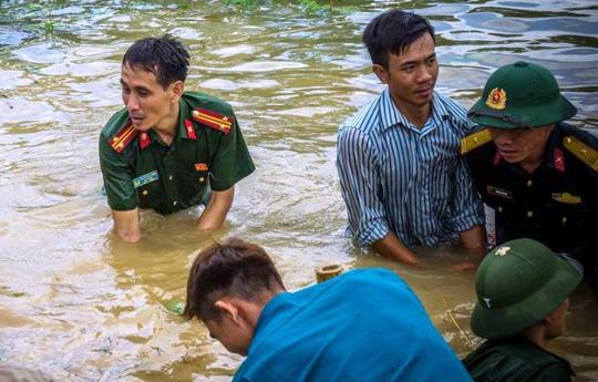 Công an, bộ đội dầm mình trong nước ăn vội, giúp dân chống lũ dữ - Ảnh 1.