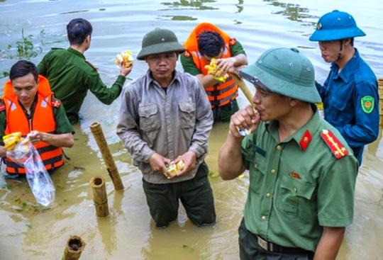 Công an, bộ đội dầm mình trong nước ăn vội, giúp dân chống lũ dữ - Ảnh 10.