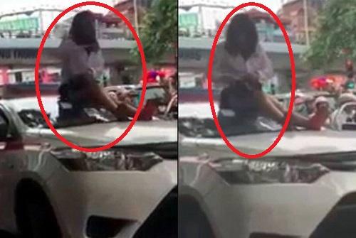 Bị CSGT dừng xe vì vượt đèn đỏ, nữ tài xế taxi trèo lên nóc xe ăn vạ - Ảnh 1.