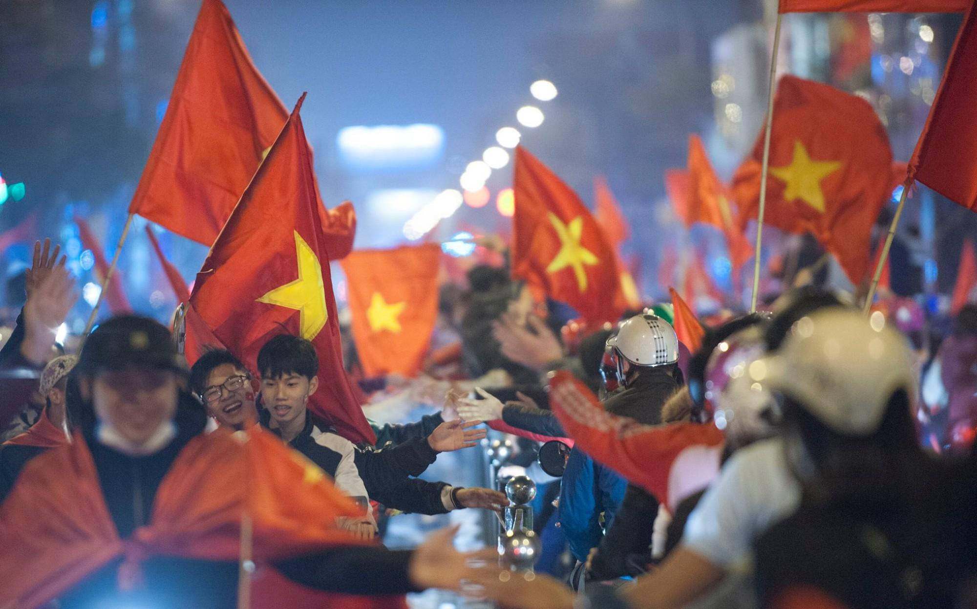 Ảnh: Chỉ cái chạm tay thôi đã đủ thấy tinh thần dân tộc và tình yêu bóng đá của hàng triệu người hâm mộ Việt Nam rồi!