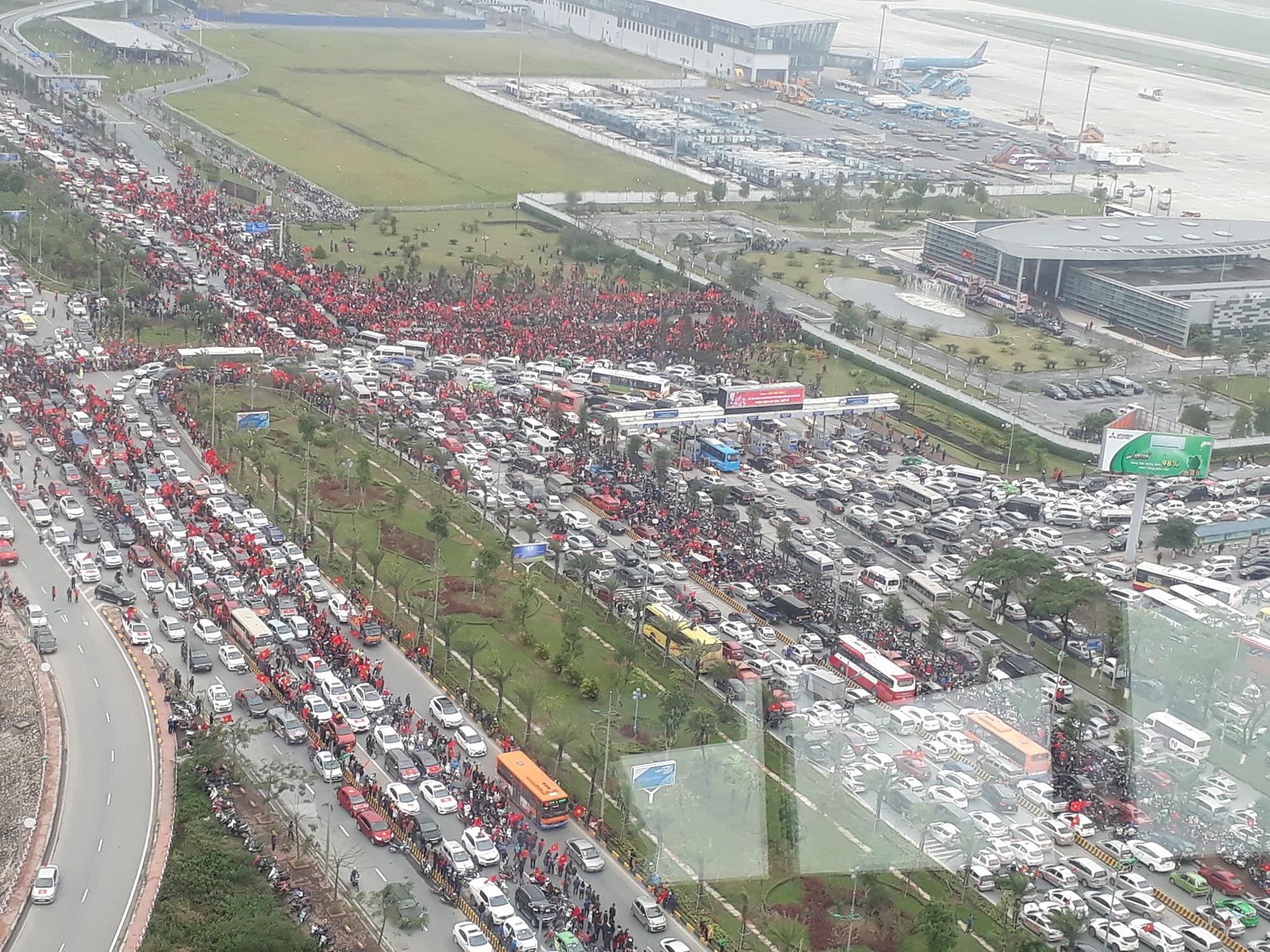 Dù sân bay Nội Bài chật kín, nhiều hành khách vẫn vui vẻ kéo vali đi bộ hơn 1km để vào nhà ga T2 - Ảnh 1.