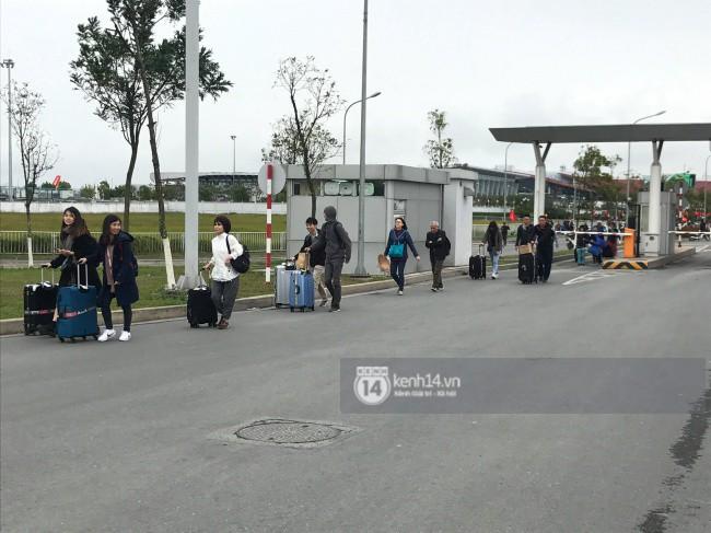 Dù sân bay Nội Bài chật kín, nhiều hành khách vẫn vui vẻ kéo vali đi bộ hơn 1km để vào nhà ga T2 - Ảnh 4.