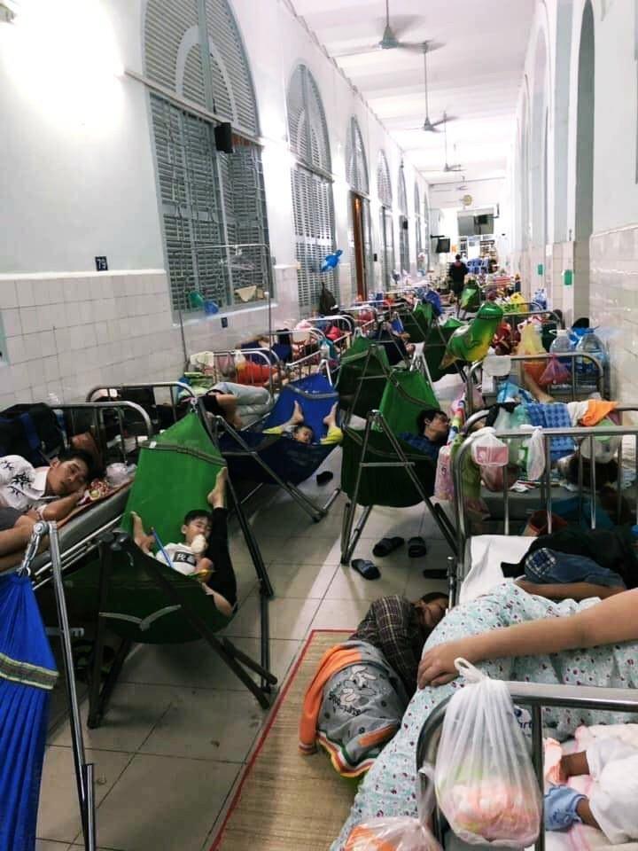 Xót xa hình ảnh người lớn và trẻ em trải chiếu, mắc võng nằm chật kín hành lang bệnh viện ở Sài Gòn - Ảnh 1.