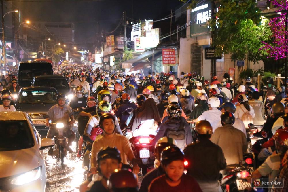 Kẹt xe kinh hoàng sau cơn mưa chiều ở Sài Gòn, trẻ em mệt mỏi ngủ trên xe máy - Ảnh 4.