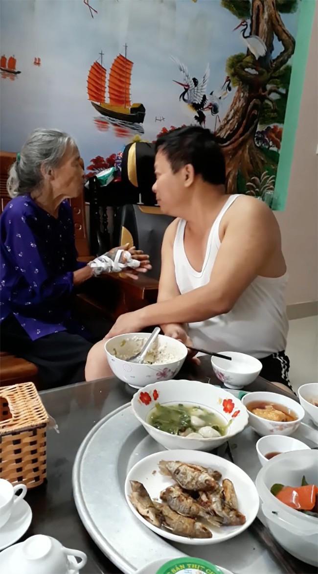 Chú Sỹ vừa nhẹ nhàng xúc cơm cho mẹ ăn, vừa nói chuyện và hát Xoan cùng mẹ. (Ảnh: Cắt từ clip)