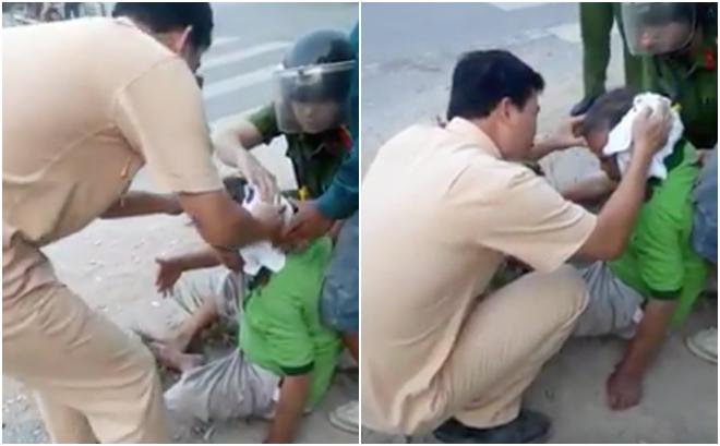 Chiến sĩ CSGT giữ chặt chiếc áo trên đầu nạn nhân để cầm máu - Ảnh cắt từ clip