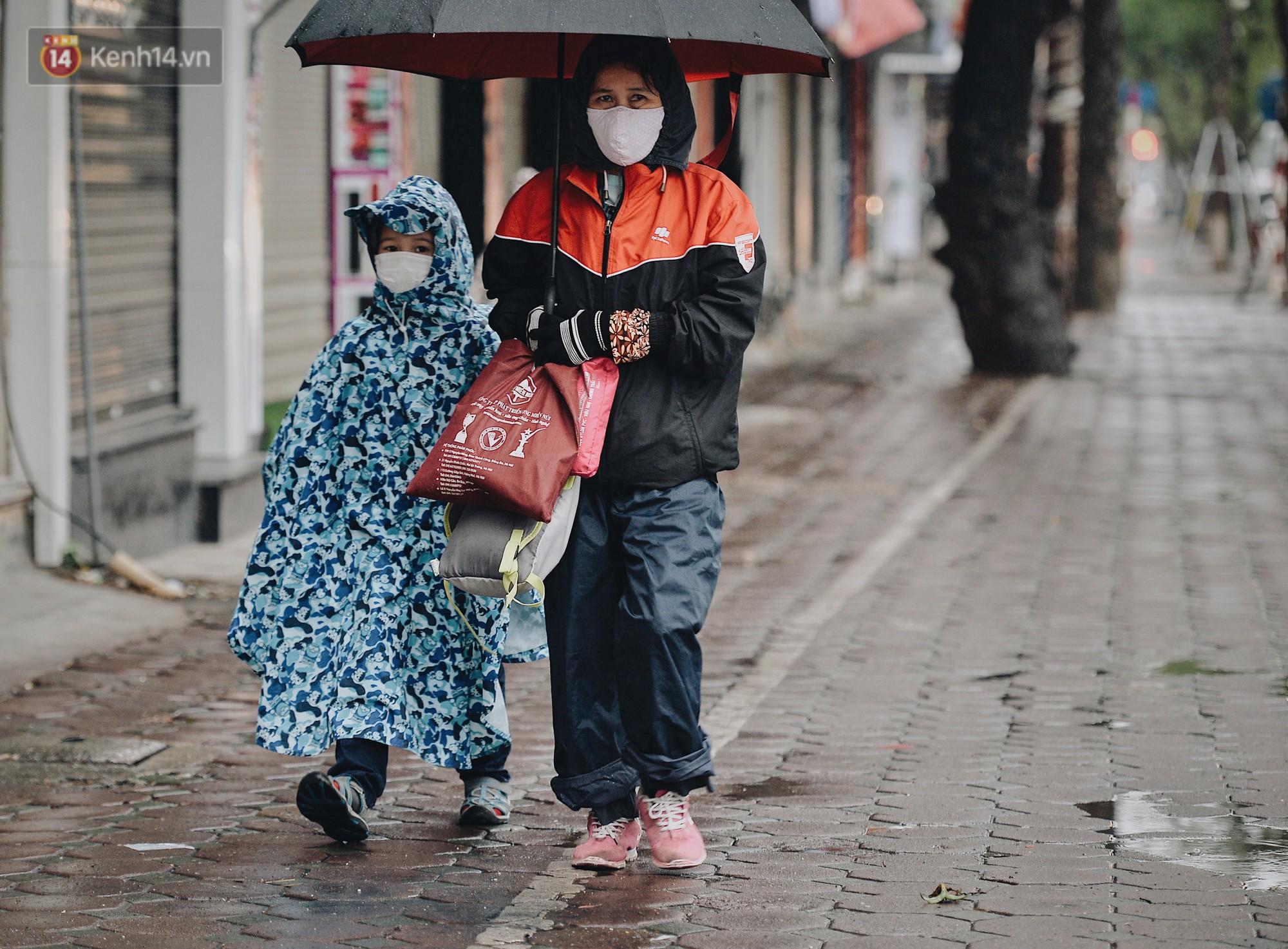 Chùm ảnh: Sau một đêm trở gió Hà Nội mưa lạnh xuống đến 17 độ C, người dân co ro ra đường - Ảnh 2.