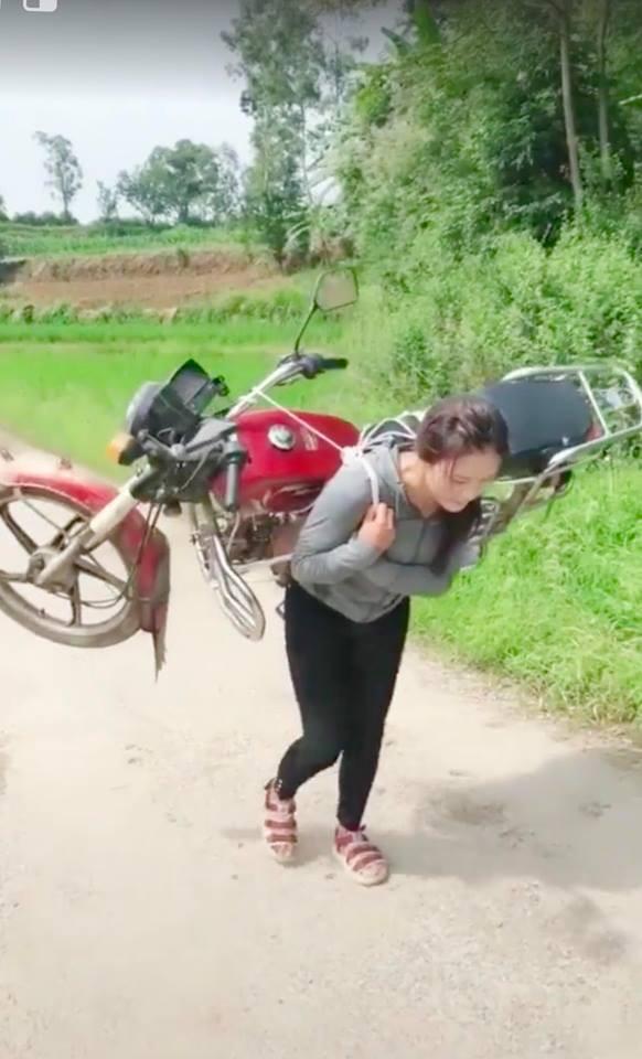 Cô gái cõng cả chiếc xe máy trên lưng nhẹ nhàng như một chiếc balo khiến cánh đàn ông thán phục - Ảnh 2.