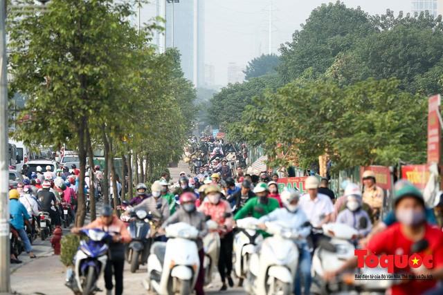 Né tắc đường, người dân Thủ đô không ngại tập thể dục buổi sáng bằng cách dắt xe máy hàng trăm mét - Ảnh 1.