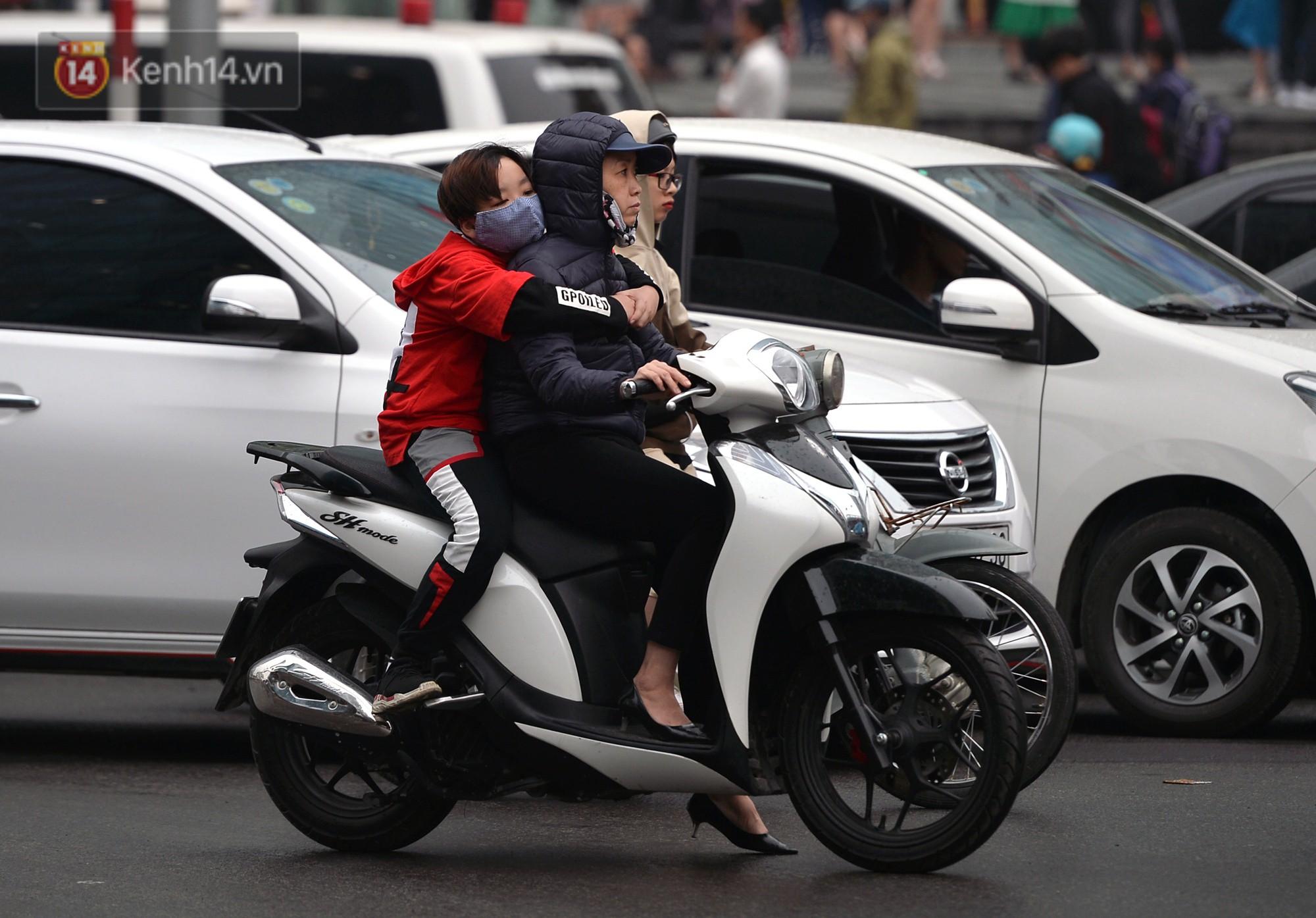 Chùm ảnh: Hà Nội giảm nhiệt độ, người mặc áo khoác dày, người quần đùi áo cộc xuống phố - Ảnh 3.