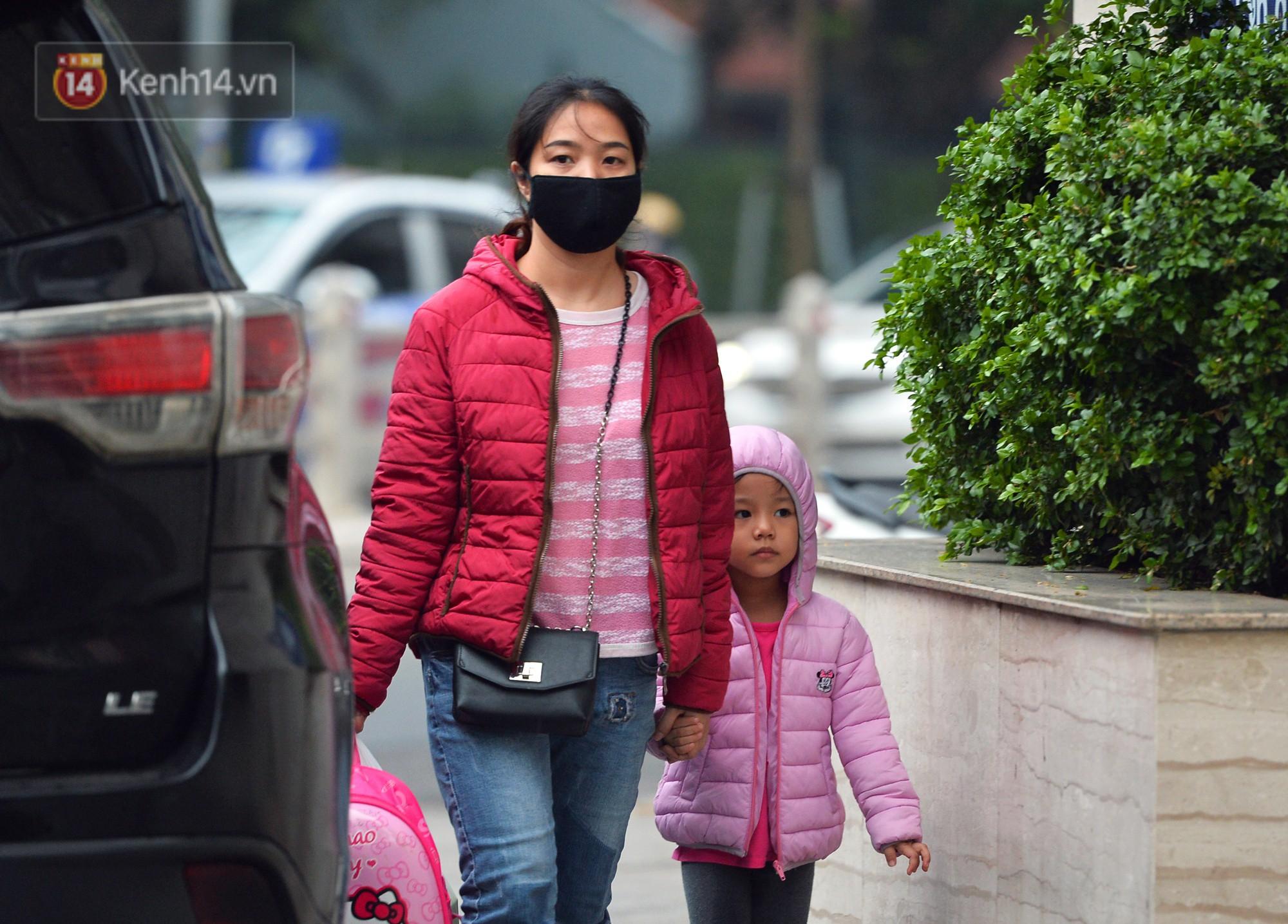 Chùm ảnh: Hà Nội giảm nhiệt độ, người mặc áo khoác dày, người quần đùi áo cộc xuống phố - Ảnh 2.
