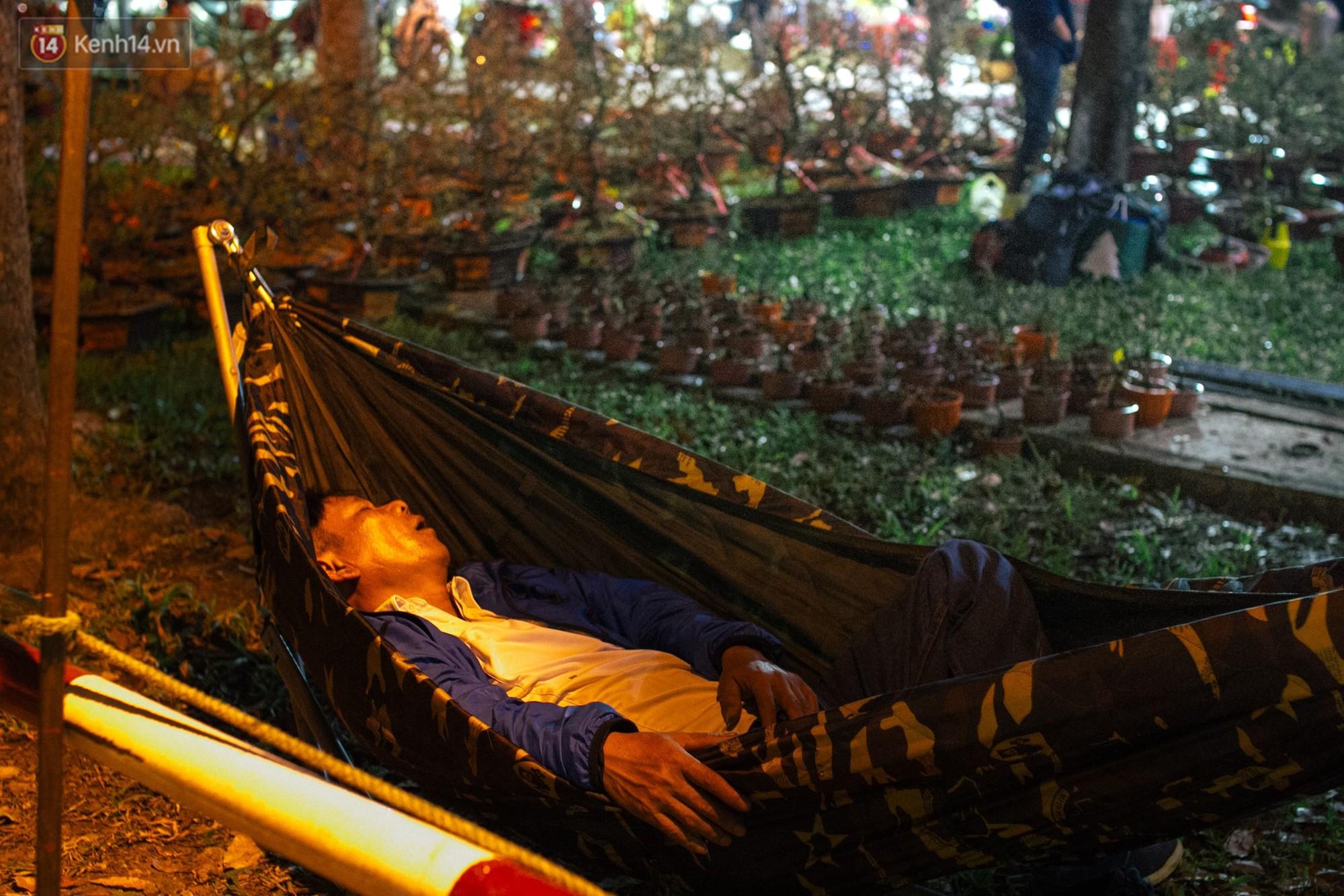 Chùm ảnh: Sợ mất trộm, nhiều gia đình tiểu thương dựng lều mắc võng, thay phiên nhau thức đêm để canh hoa Tết - Ảnh 14.