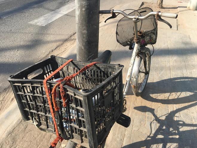 Chiếc xe đạp cũ kỹ chở vài ba lon bia của cụ.