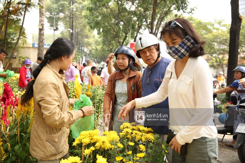 Một số người dân đứng chọn lựa mặc cả để mua hoa cúc
