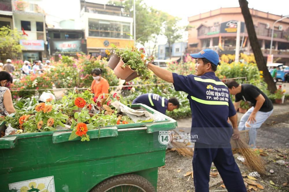 Một số công nhân môi trường bắt đầu dọn dẹp số hoa bị đập nát lên xe rác
