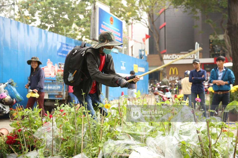 Một tiểu thương đang tự tay đập bỏ những chậu hoa chưa bán hết của mình