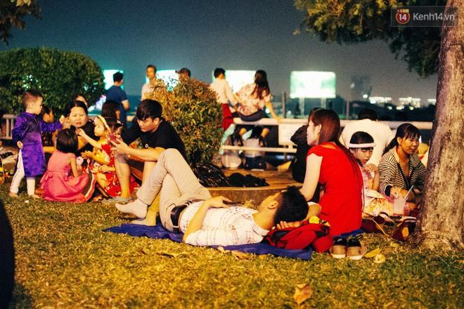 Một số người dân nằm dài ra thảm cỏ chờ đợi xem pháo hoa. Ảnh: Hữu Nghĩa.