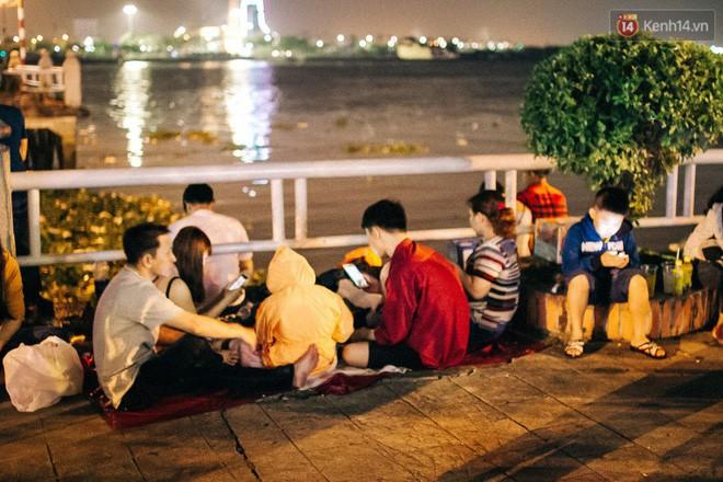 Nhiều bạn trẻ trải chiếu ngồi cạnh bến Bạch Đằng háo hức chờ thời khắc chào năm 2018. Ảnh: Hữu Nghĩa.