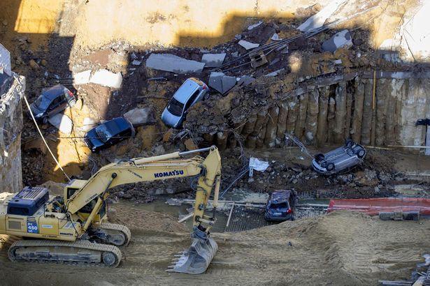 Chỉ sau một đêm, người dân bàng hoàng nhìn hố sâu 9m khổng lồ nuốt gọn nhiều ô tô, nhà cửa - Ảnh 1.