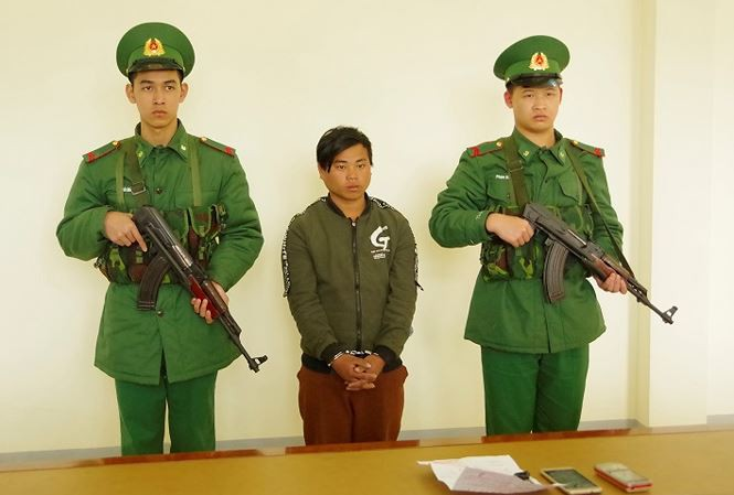 Sùng Seo Tráng (giữa) nghe đọc lệnh bắt tại Đồn Biên phòng Cửa khẩu quốc tế Lào Cai