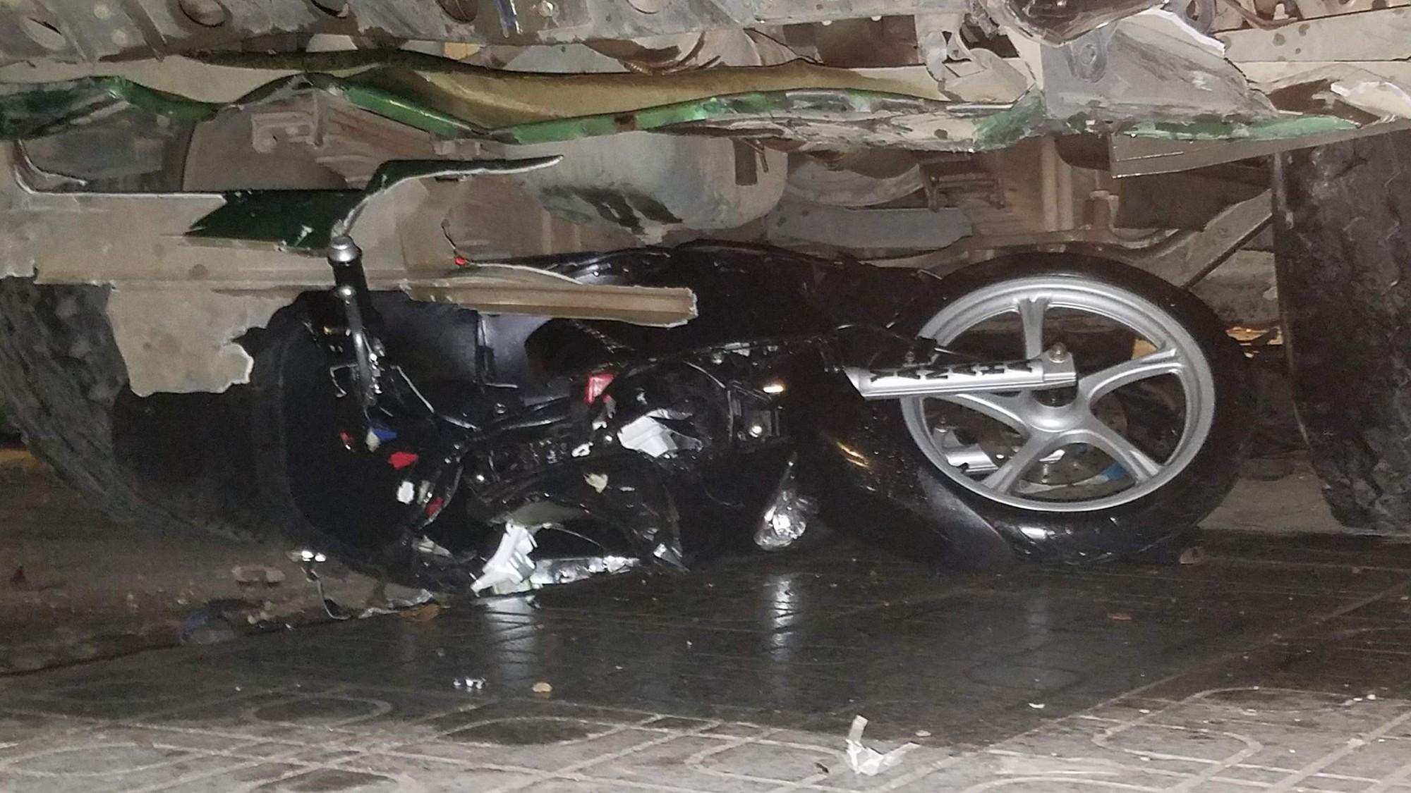Một chiếc xe máy bị cuốn vào gầm xe, biến dạng