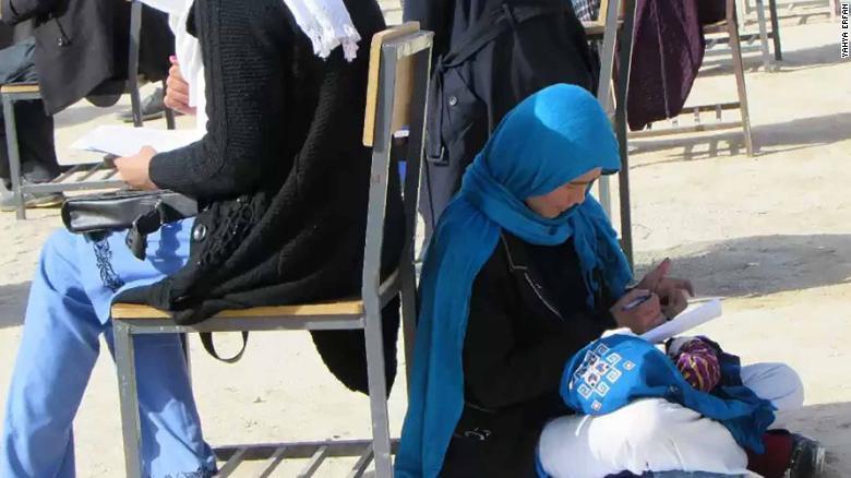 Bức ảnh nữ sinh ôm con ngồi bệt dưới đất làm bài thi đại học gây xúc động - Ảnh 2.