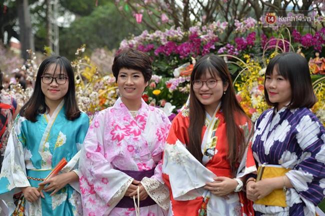 Hàng ngàn người dân Hà Nội chen chúc trong buổi sáng đầu tiên mở cửa Lễ hội hoa anh đào - Ảnh 6.