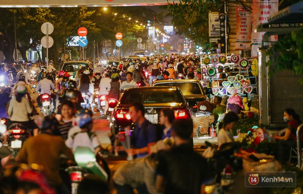 Chùm ảnh: Sợ ế hoa 8/3, sinh viên Sài Gòn tràn xuống lòng đường cố mời khách ghé mua - Ảnh 1.